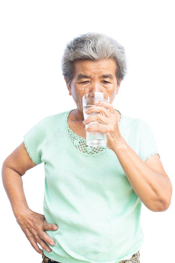 Lycklig gammal kvinna som dricker sötvatten av exponeringsglas fotografering för bildbyråer