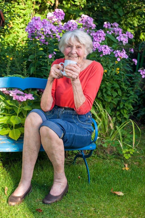 Lycklig gammal kvinna som har ett kaffe på trädgården arkivfoto