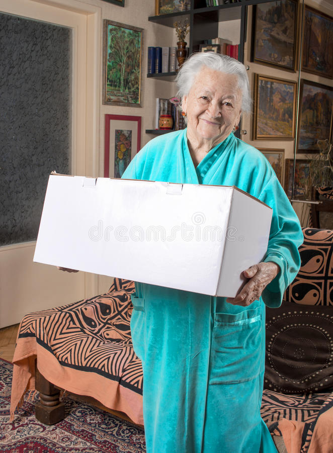 Lycklig gammal kvinna som rymmer en stor kartong arkivbild