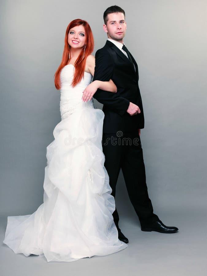 Lycklig gift parbrudbrudgum på grå bakgrund royaltyfri fotografi