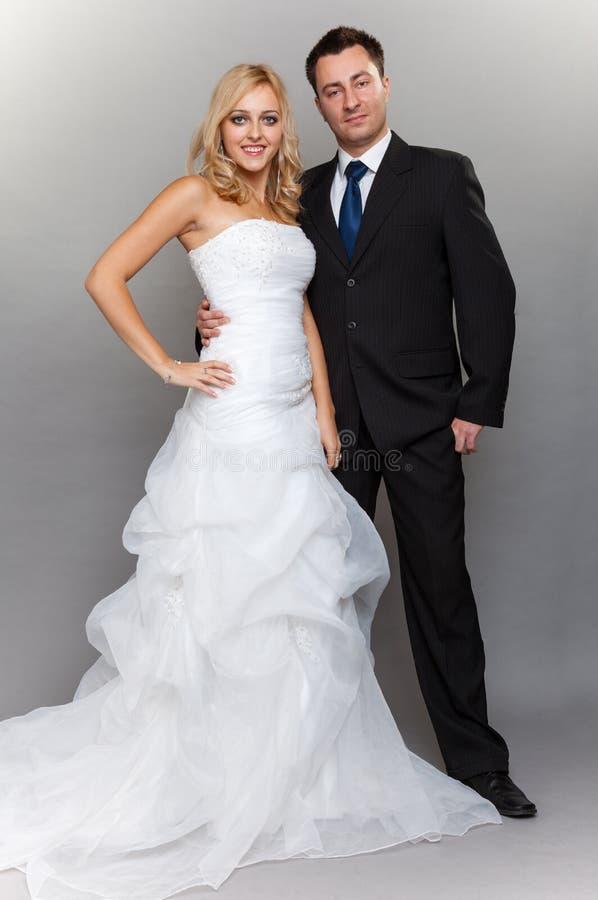 Lycklig gift parbrudbrudgum på grå bakgrund arkivfoton