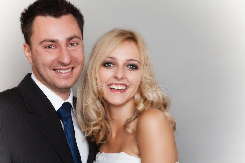 Lycklig gift parbrudbrudgum på grå bakgrund royaltyfri foto