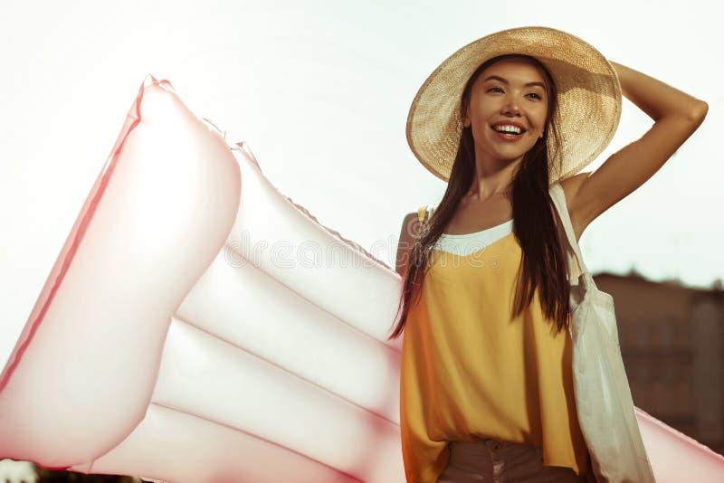 Lycklig glödande le kvinna som rymmer den uppblåsbara luftmadrassen för att simma royaltyfria bilder