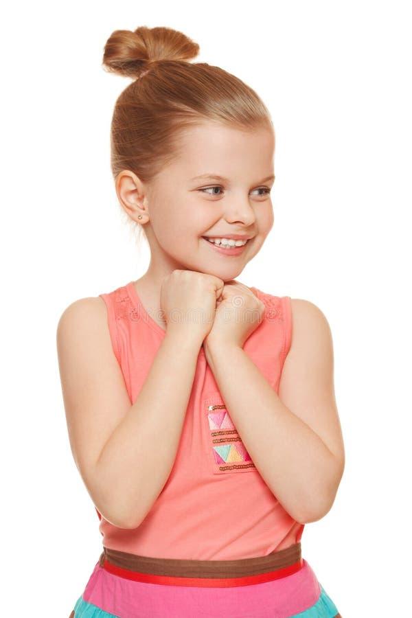Lycklig glad liten flicka som från sidan ser i spänningen som isoleras på vit bakgrund arkivfoton