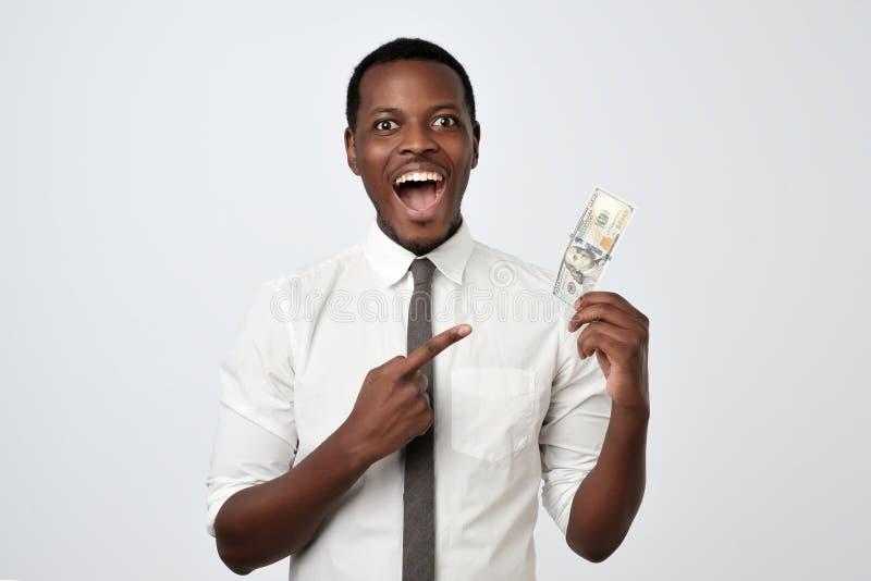 Lycklig glad stilig ung vuxen affärsman som rymmer dollar och öppnar munnen royaltyfria bilder