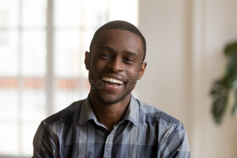 Lycklig gladlynt afrikansk millennial man som hemma ser kameran arkivfoton