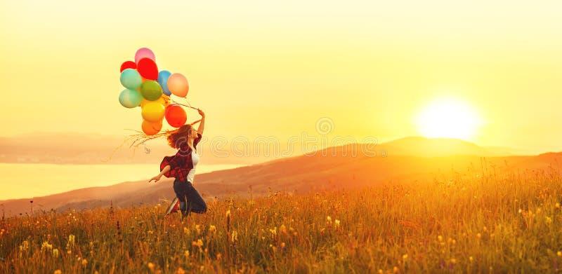 Lycklig gladlynt flicka med ballonger som stöter ihop med ängen på sunse royaltyfria bilder