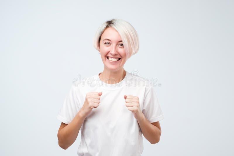 Lycklig gladlynt fröjd för ung kvinna på den positiva nyheterna- eller födelsedaggåvan och att se med glat och charmigt leende arkivfoto