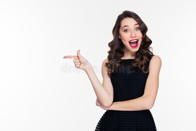 Lycklig gladlynt härlig ung kvinnlig med den retro frisyren som bort pekar royaltyfria bilder