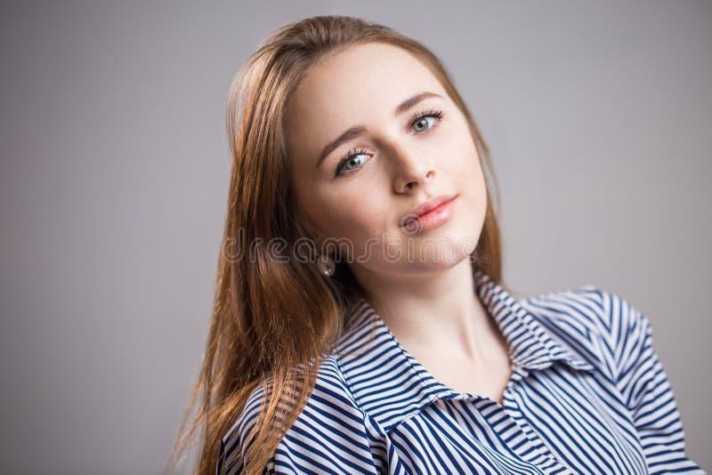 Lycklig gladlynt ung kvinna som bär hennes randiga blått- och vitskjorta som ser kameran med det glade och charmiga leendet, stud royaltyfria bilder