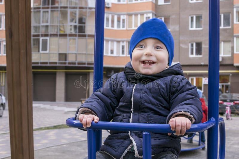 Lycklig gladlynt unge som svänger på lekplats arkivbilder