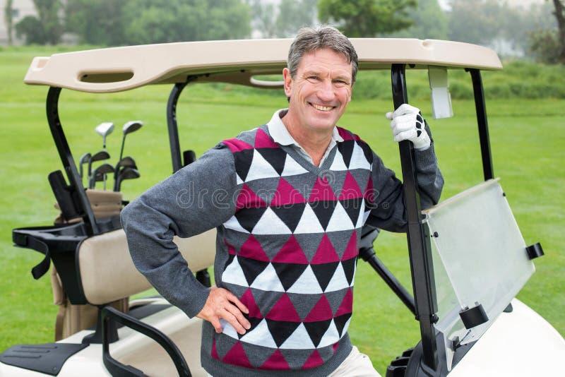 Lycklig golfare bredvid hans golfbarnvagn fotografering för bildbyråer