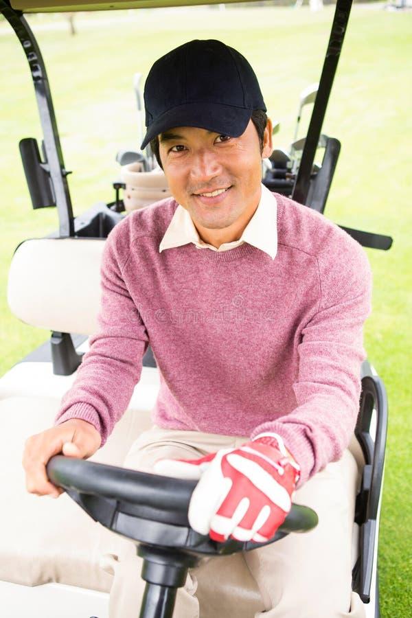 Lycklig golfare som kör hans golfbarnvagn arkivfoton
