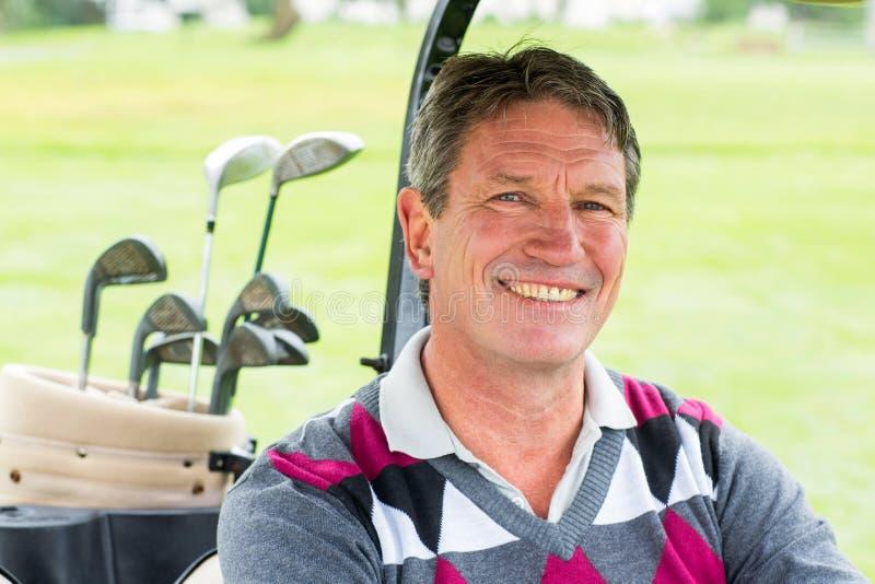 Lycklig golfare som kör hans golfbarnvagn som ler på kameran arkivbild
