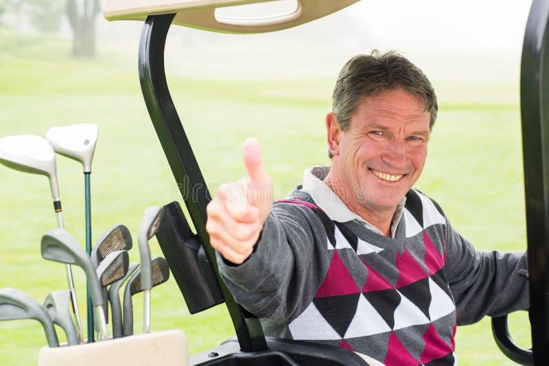 Lycklig golfare som kör hans golfbarnvagn som ler på kameran royaltyfria bilder