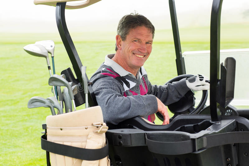 Lycklig golfare som kör hans golfbarnvagn som ler på kameran arkivfoto