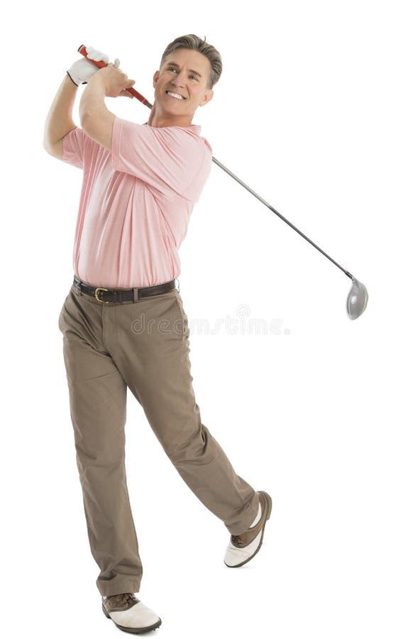 Lycklig golfare som ser bort, medan svänga golfklubben royaltyfria foton