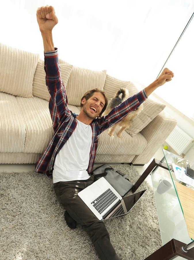 Lycklig grabb med bärbara datorn som är jublande i rymlig vardagsrum royaltyfria foton