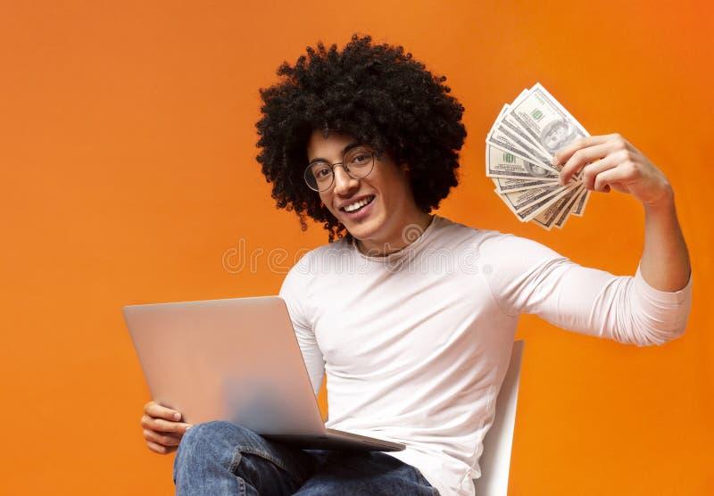 Lycklig grabb som arbetar på bärbara datorn och visar gruppen av pengar arkivbild