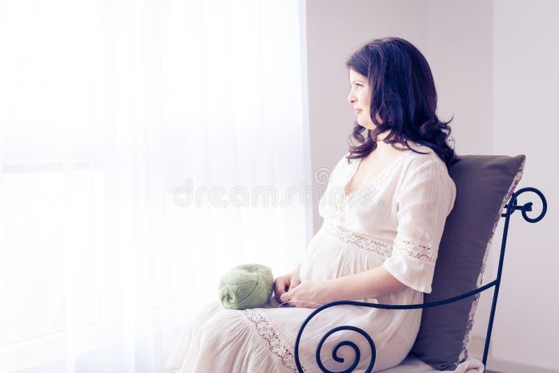 Lycklig gravid kvinna i den vita klänningen fotografering för bildbyråer