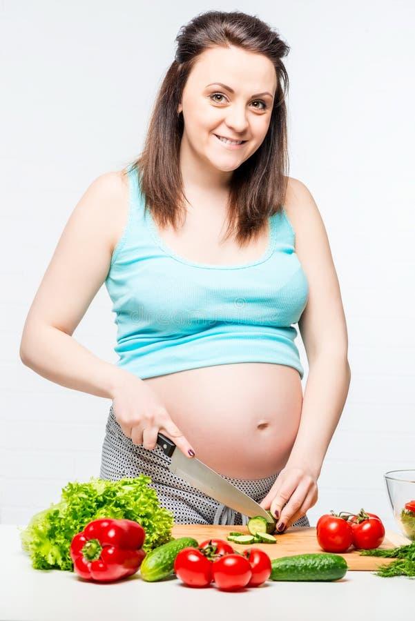 Lycklig gravid kvinna i köket som förbereder en sallad arkivbilder
