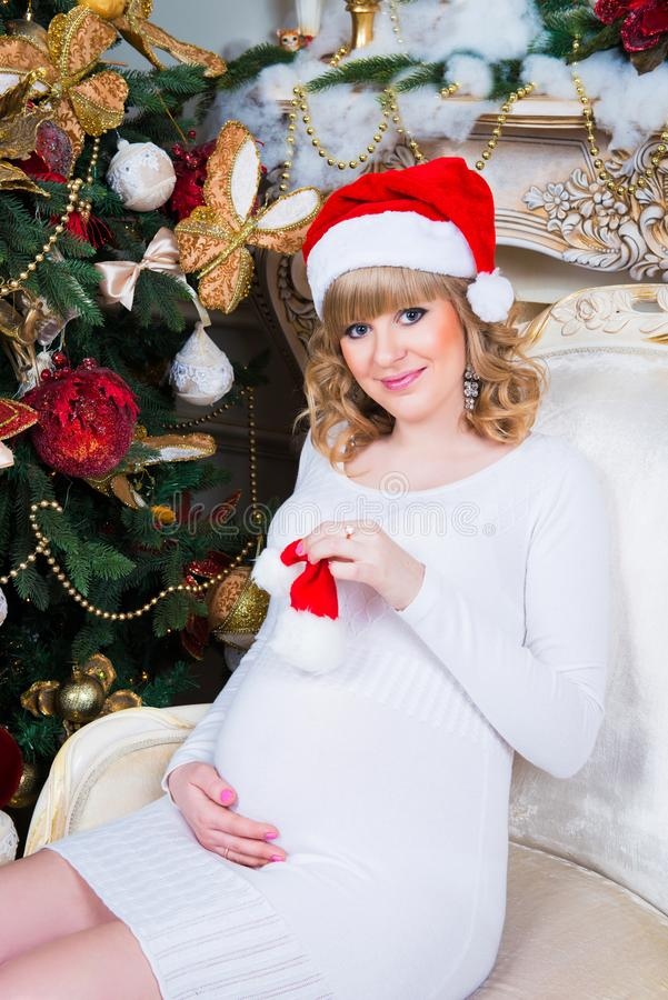 Lycklig gravid kvinna med gåvor nära julträdet royaltyfria bilder