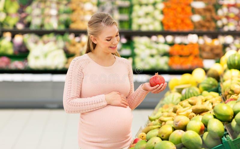 Lycklig gravid kvinna med granatäpplet på livsmedelsbutiken royaltyfria bilder