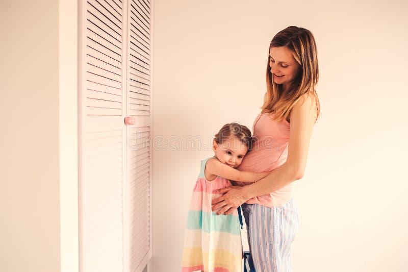 Lycklig gravid kvinna med hennes litet barndotter hemma arkivfoto