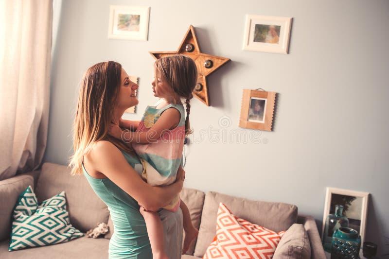Lycklig gravid kvinna med hennes litet barndotter hemma royaltyfri bild