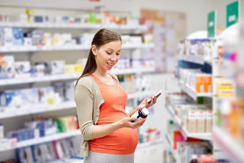 Lycklig gravid kvinna med smartphonen på apotek arkivbild