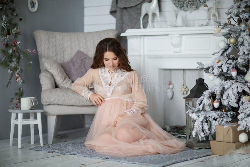 Lycklig gravid kvinna nära jultreen arkivbild