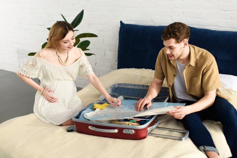 lycklig gravid kvinna och make som ser översikten och inpackning royaltyfria foton