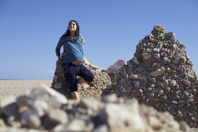 Lycklig gravid gravid kvinna på stranden arkivfoton