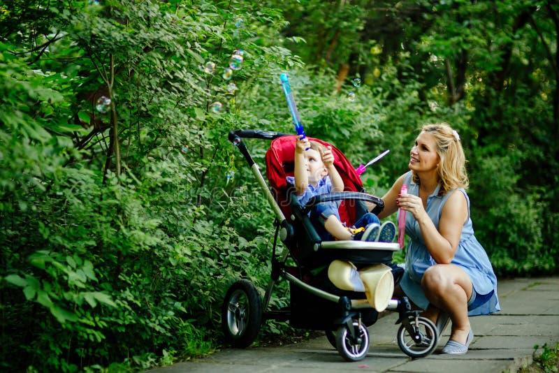 Lycklig gravid kvinna som blåser såpbubblor med barnet royaltyfria foton