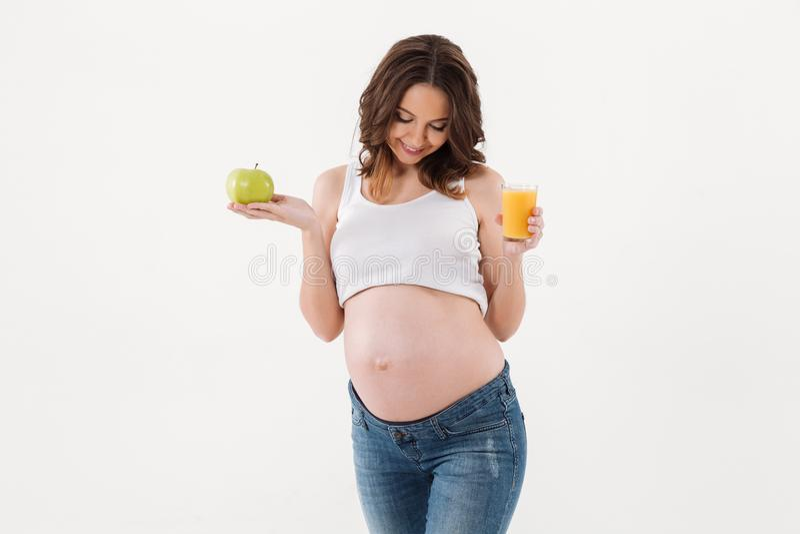 Lycklig gravid kvinna som dricker fruktsaft åt sidan se arkivfoton