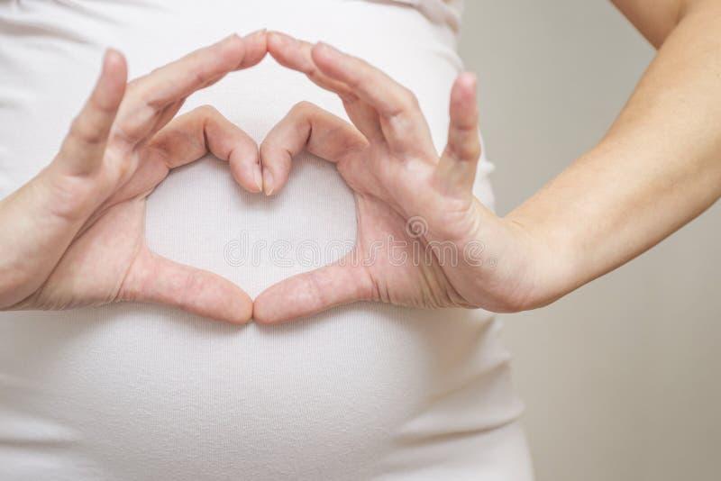 Lycklig gravid kvinna som gör tecknet för hjärtaformhand på hennes mage Gravid kvinnas buk med fingerhjärtasymbol royaltyfri foto