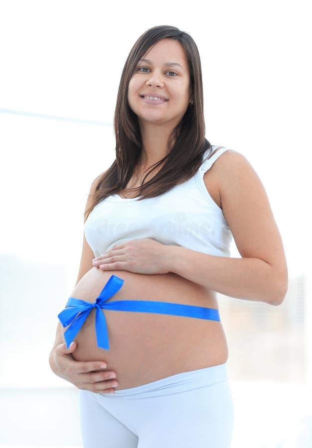 Lycklig gravid kvinna som mäter hennes mage och midja royaltyfri fotografi