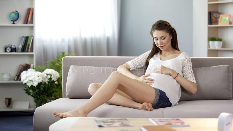 Lycklig gravid kvinna som sitter på soffan som ömt trycker på buken, söt havandeskap royaltyfri fotografi