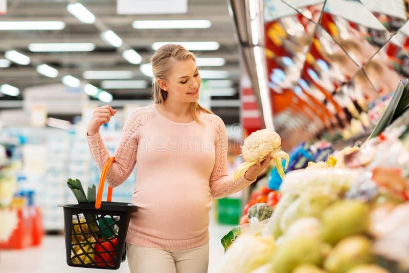 Lycklig gravid kvinnaköpandeblomkål på livsmedelsbutiken royaltyfri bild