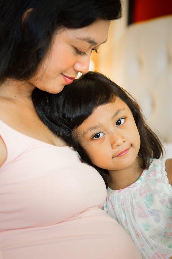 Lycklig gravid moder och dotter arkivfoton