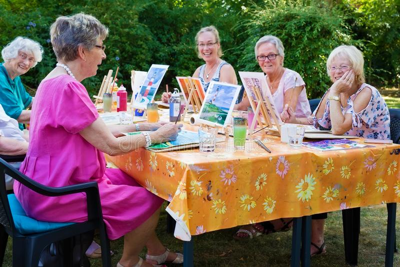 Lycklig grupp av höga damer som tycker om konstgrupp som placeras runt om det fria för en tabell i trädgårdmålningen med vattenfä royaltyfria foton