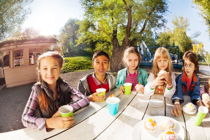 Lycklig grupp av internationella barn som dricker te royaltyfria bilder