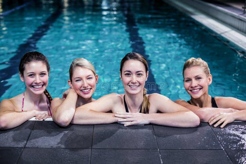 Lycklig grupp av kvinnor som lutar på poolside arkivfoton