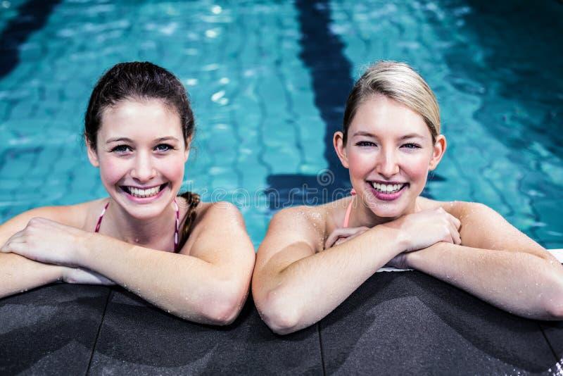 Lycklig grupp av kvinnor som lutar på poolside royaltyfri fotografi
