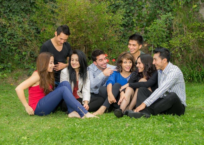Lycklig grupp av studenter som sitter på parkera royaltyfri bild