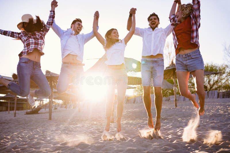 Lycklig grupp av ungdomarsom har gyckel på stranden arkivfoto