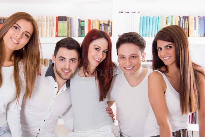 Lycklig grupp av vänner som hemma ler och kramar arkivbilder