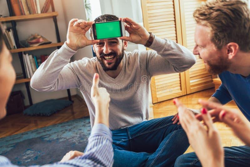 Lycklig grupp av vänner som hemma spelar charader arkivfoton