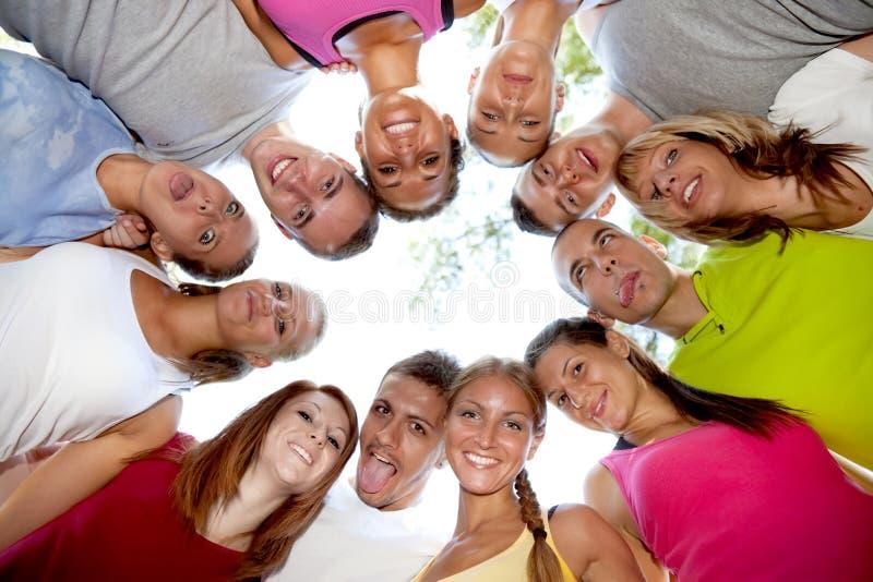 Lycklig grupp av vänner som kramar och ler royaltyfri foto