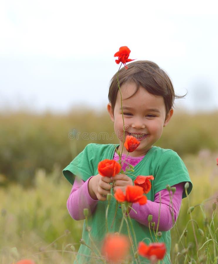 Lycklig gullig barnflicka på vallmofält Lyckliga barn royaltyfria foton